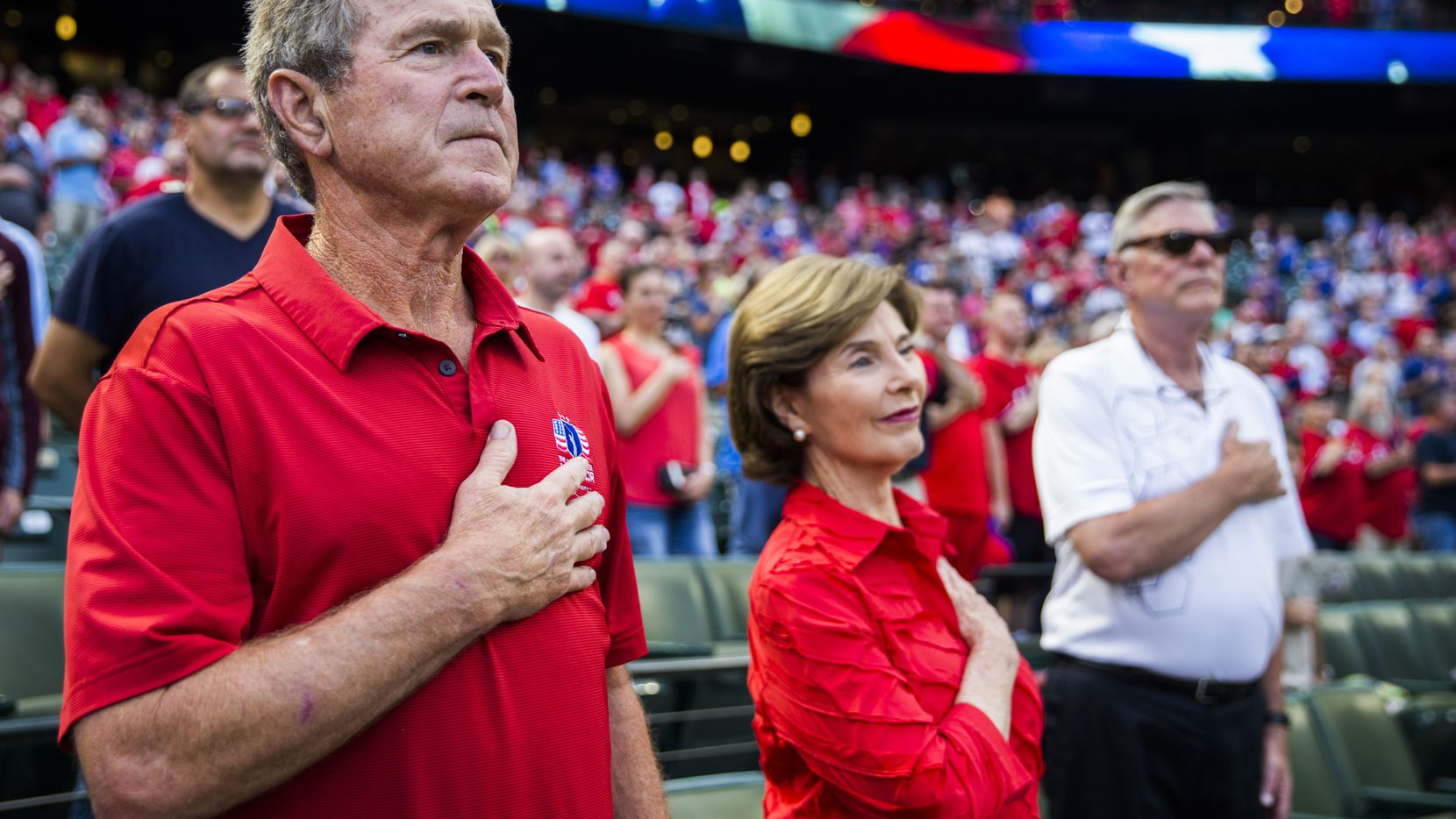 Former President George W. Bush and former first lady Laura Bush put their hands over their hearts during the singing of the national anthem before the Texas Rangers took on the Seattle Mariners on Monday, August 29, 2016 at Globe Life Park in Arlington.