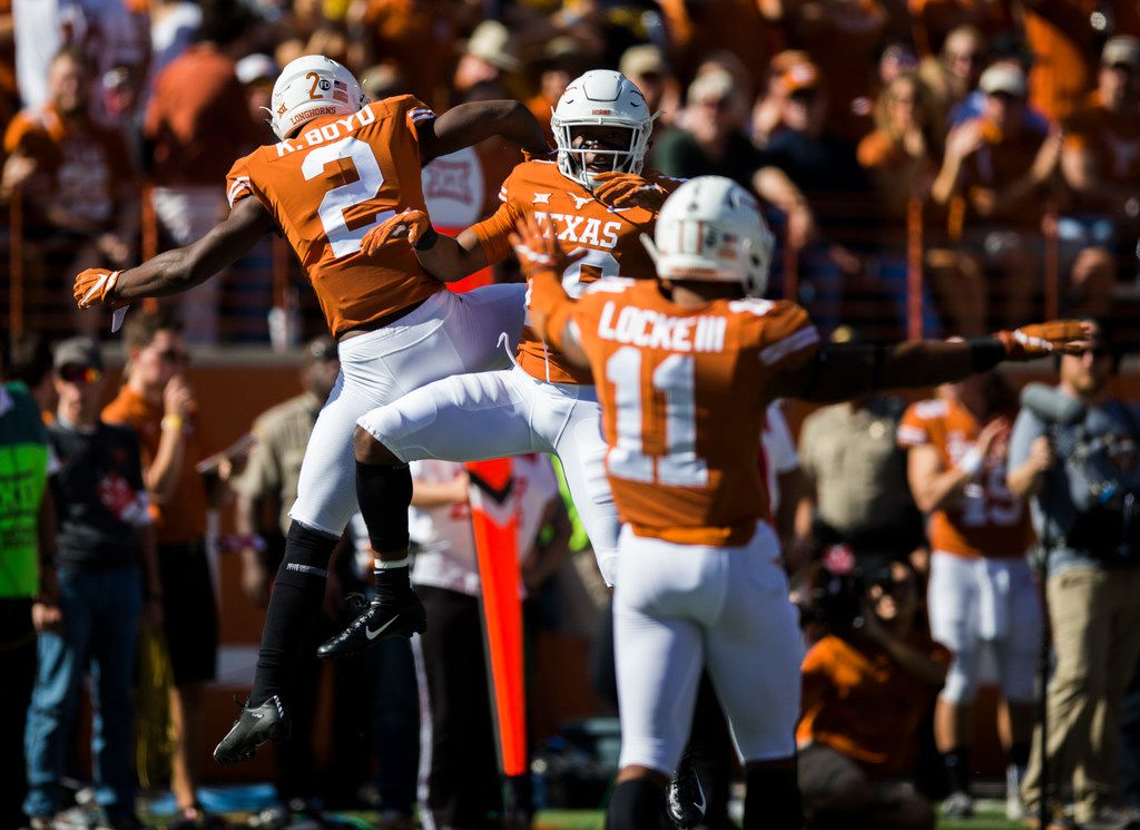 Texas Longhorns defensive back Kris Boyd (2), defensive back Josh Thompson (29) and defensive back P.J. Locke III (11) celebrate after blocking a West Virginia Mountaineers pass during the first quarter of a college football game between the University of Texas and West Virginia on Saturday, November 3, 2018 at Darrell Royal Memorial Stadium in Austin, Texas. (Ashley Landis/The Dallas Morning News)