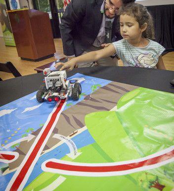 Álvaro Villa le explica a una niña cómo usar los autos robóticos. RON HEFLIN/ESPECIAL PARA DMN