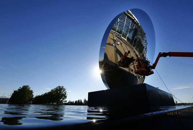 """The new """"Sky Mirror"""" sculpture by Anish Kapoor received a final polish last week prior to the official unveiling ceremony Friday night. The nearly three-stories-tall sculpture stands in the east plaza of AT&T Stadium in Arlington."""