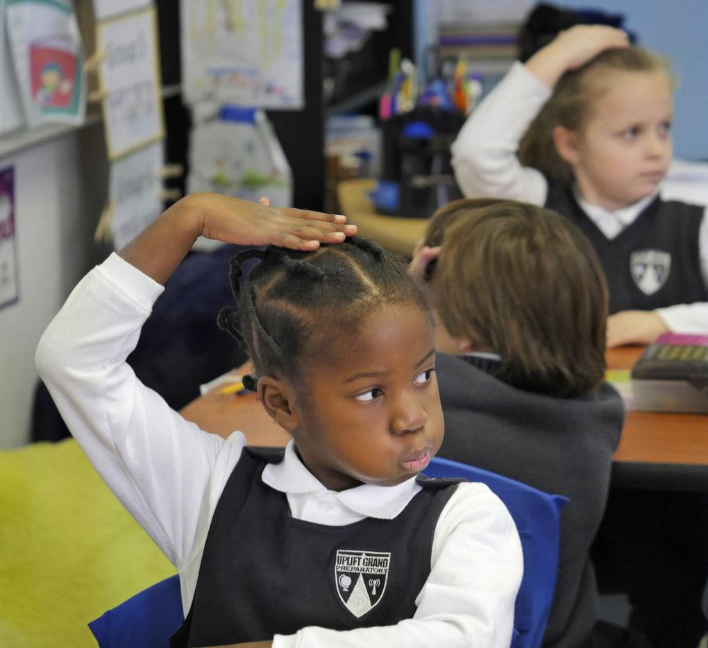 Uplift Grand Preparatory first-grade scholar Mefowe Kue, 6, patted her head in agreement with a classmate's answer in Grand Prairie on Wednesday. Uplift and GPISD are forming a public school-charter partnership next school year.