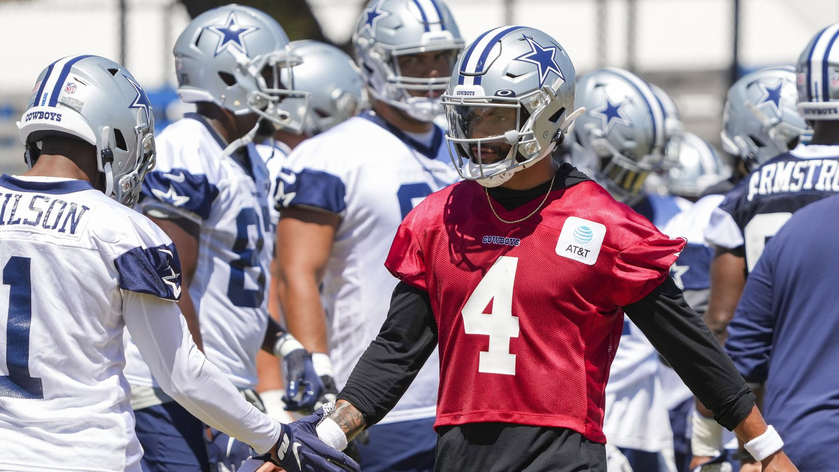 Dallas Cowboys quarterback Dak Prescott (4) slaps hands with wide receiver Cedrick Wilson (1) during a practice at training camp on Tuesday, Aug. 3, 2021, in Oxnard, Calif.