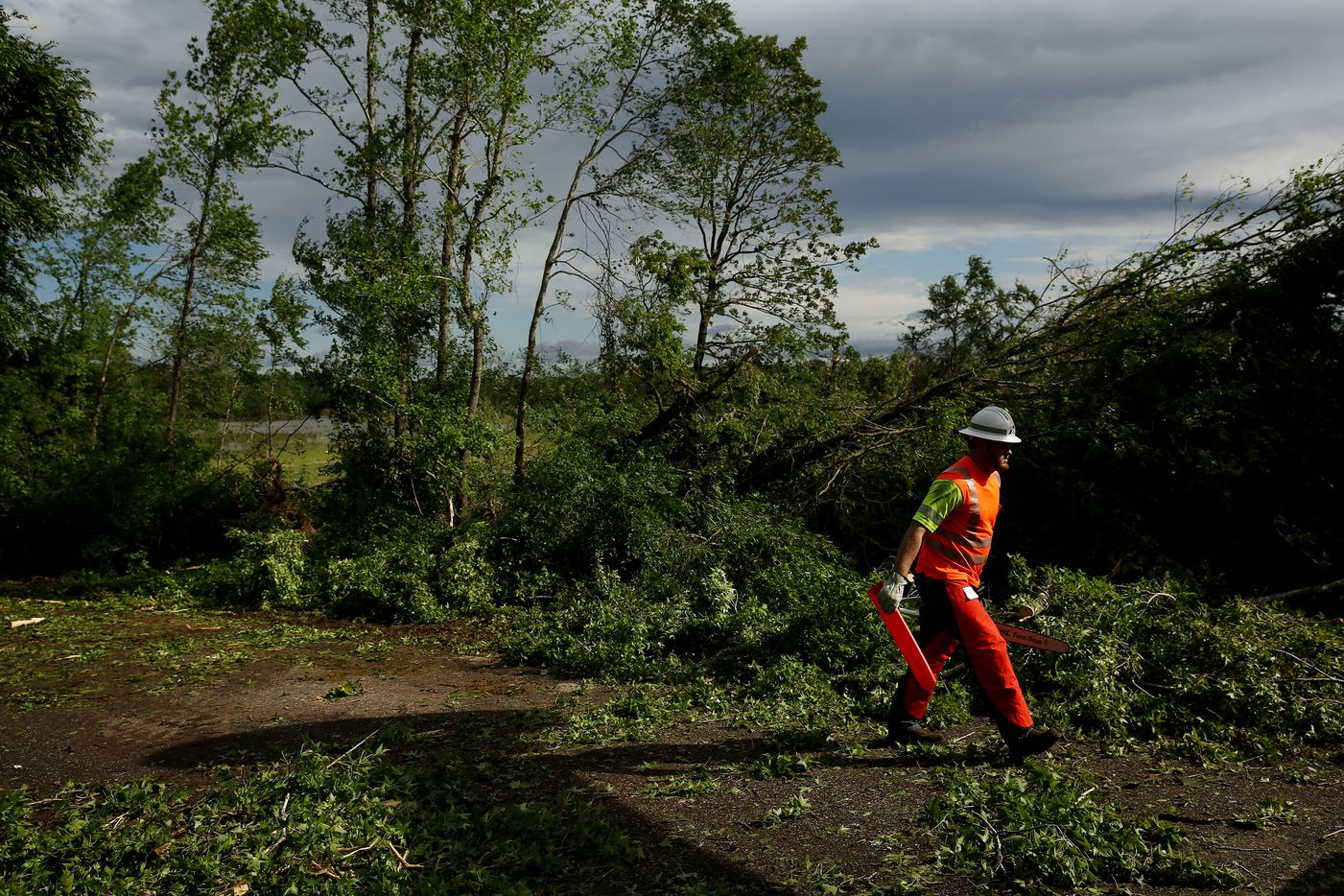 Ethan O'Donnell, of a Texas Department of Transportation crew out of Mineola, prepares to use a chainsaw to clear debris on VZ County Road 1106. (Andy Jacobsohn/The Dallas Morning News)
