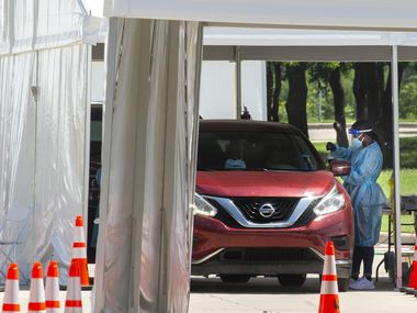 Medical personnel prep and conduct a nasal swab test to visitors of the drive-thru COVID-19 testing site located at the University of Dallas campus in Dallas on Friday, July 10, 2020.