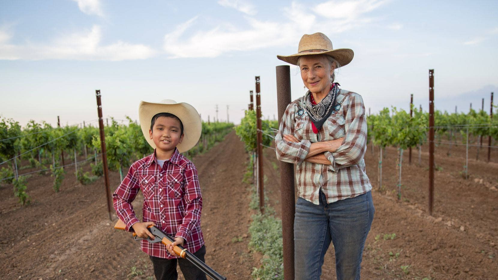 Andis Applewhite and nephew Calvin Wallace Gloria, 8, holding his BB gun, stand in Applewhite's West Texas vineyard that she says has been damaged by exposure to a chemical used in nearby cotton fields.