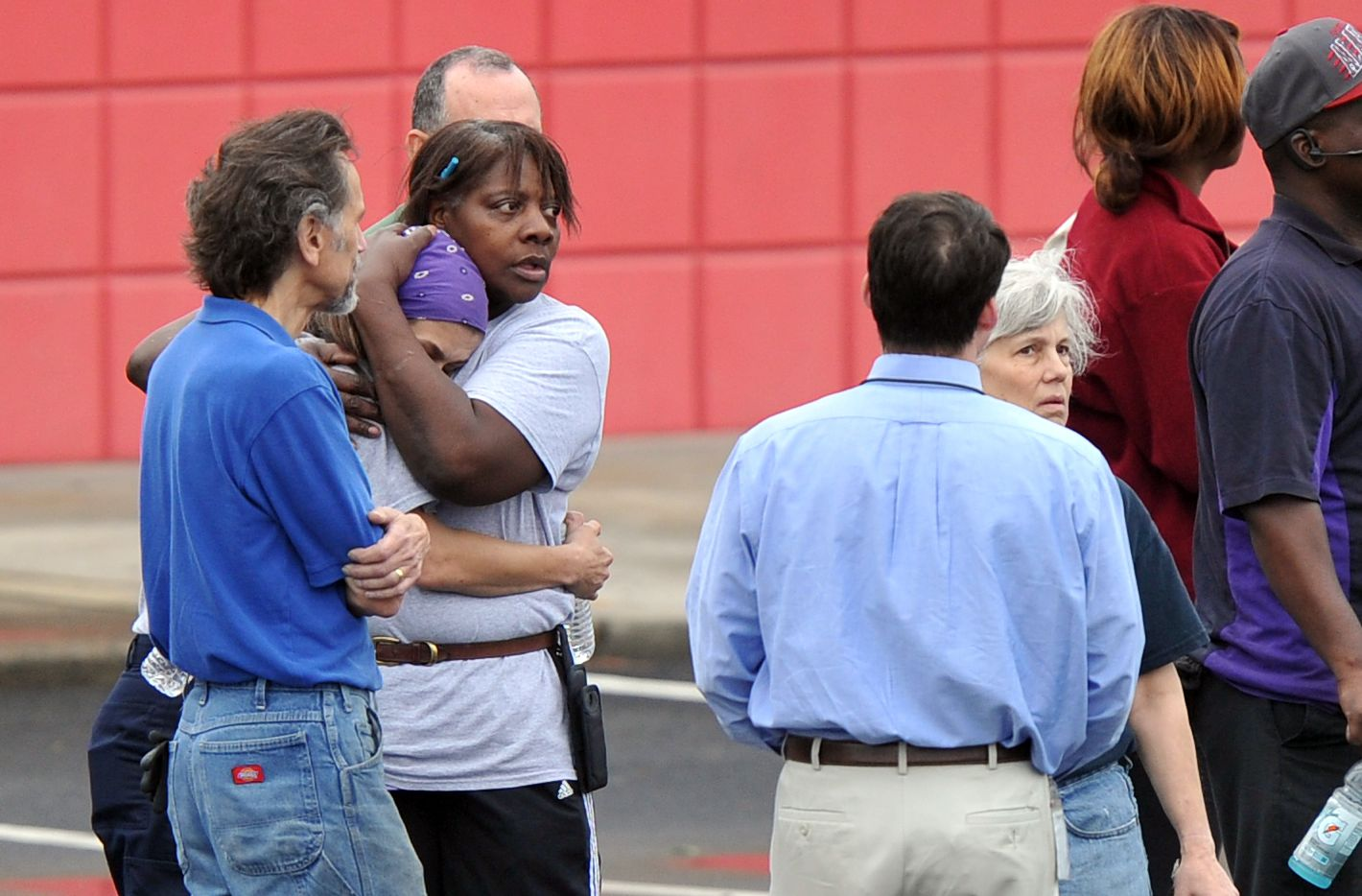 FedEx employee Lisa Aiken, wearing bandana, is embraced by a co-worker as other employees gather at a skating rink following a shooting at a FedEx facility in Kennesaw, Ga., on Tuesday.