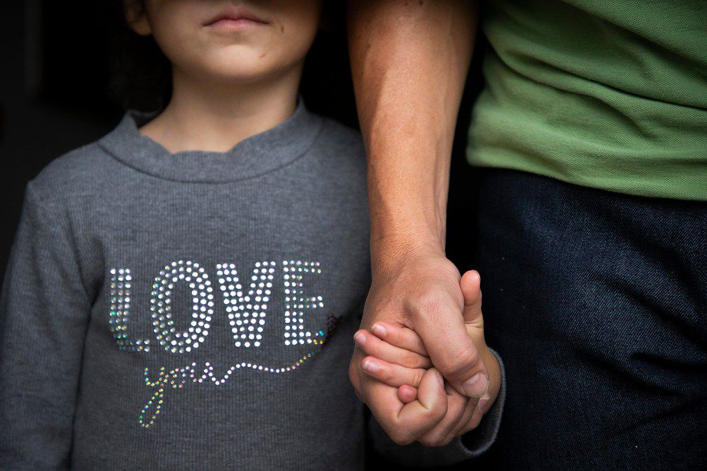 Edwin Romero, a 56-year-old Honduran immigrant father who was separated from his daughter at the border in May, holds her hand at his family's apartment in Houston.