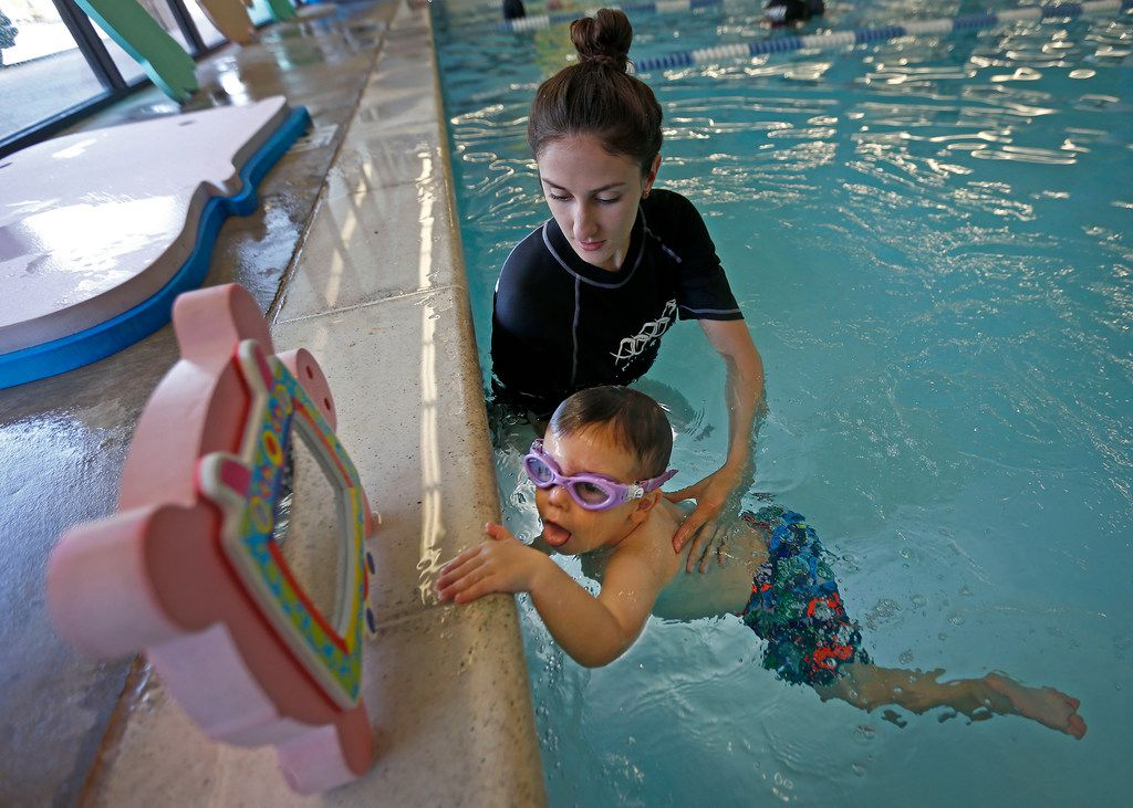 Instructor Ashlee Brannam teaches Truett Roush, 2, how to go back to the wall of the pool during a swim lesson at Jim Montgomery Swim School in Dallas.