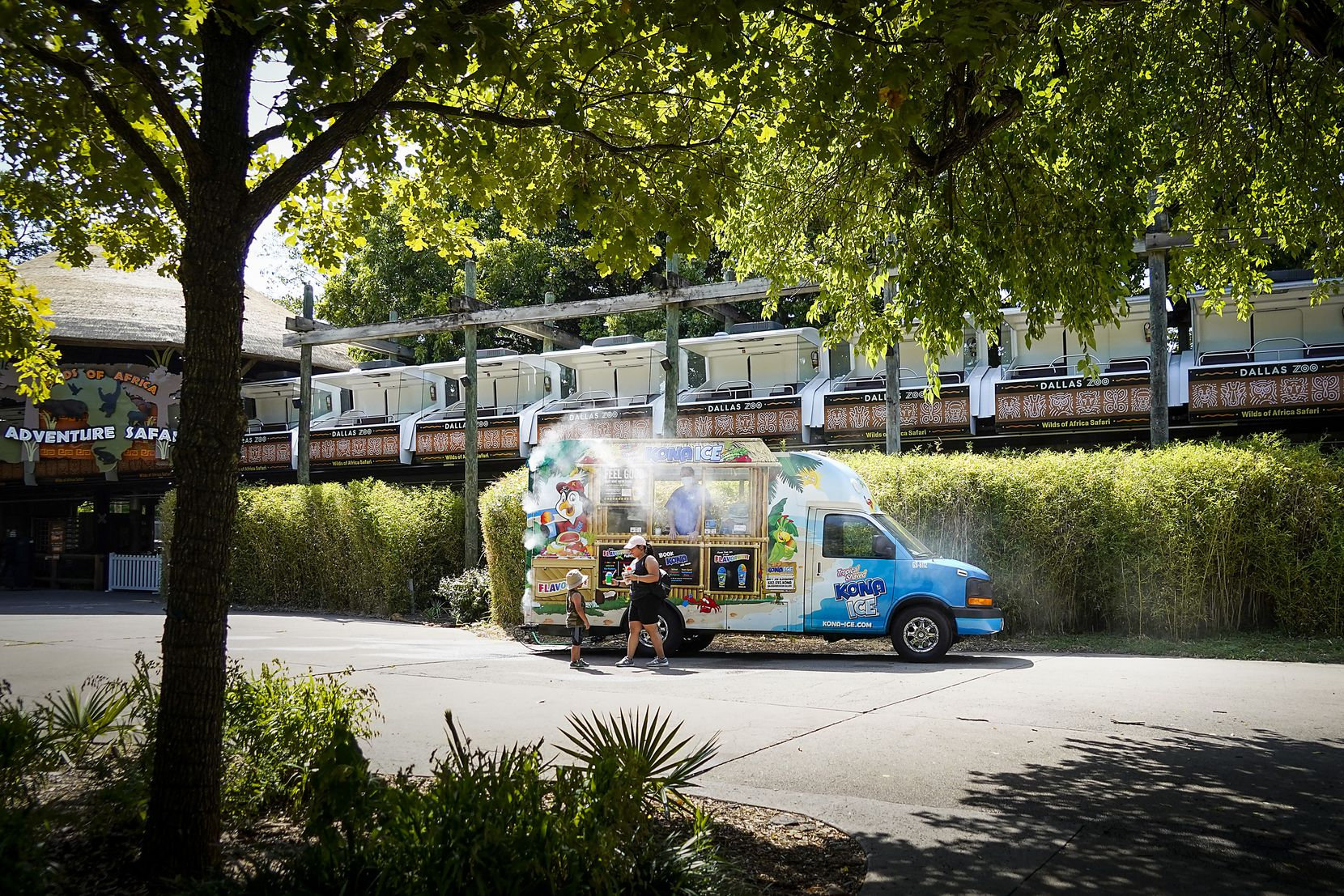 Guests stop for shaved ice beneath the Adventure Safari Monorail at the Dallas Zoo on Thursday.