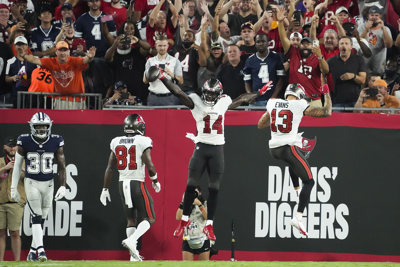 Tampa Bay Buccaneers wide receiver Chris Godwin (14) celebrates a touchdown catch with wide receiver Antonio Brown (81) and wide receiver Mike Evans (13) as Dallas Cowboys cornerback Anthony Brown (30) looks on during the first half of an NFL football game at Raymond James Stadium on Thursday, Sept. 9, 2021, in Tampa, Fla. (Smiley N. Pool/The Dallas Morning News)