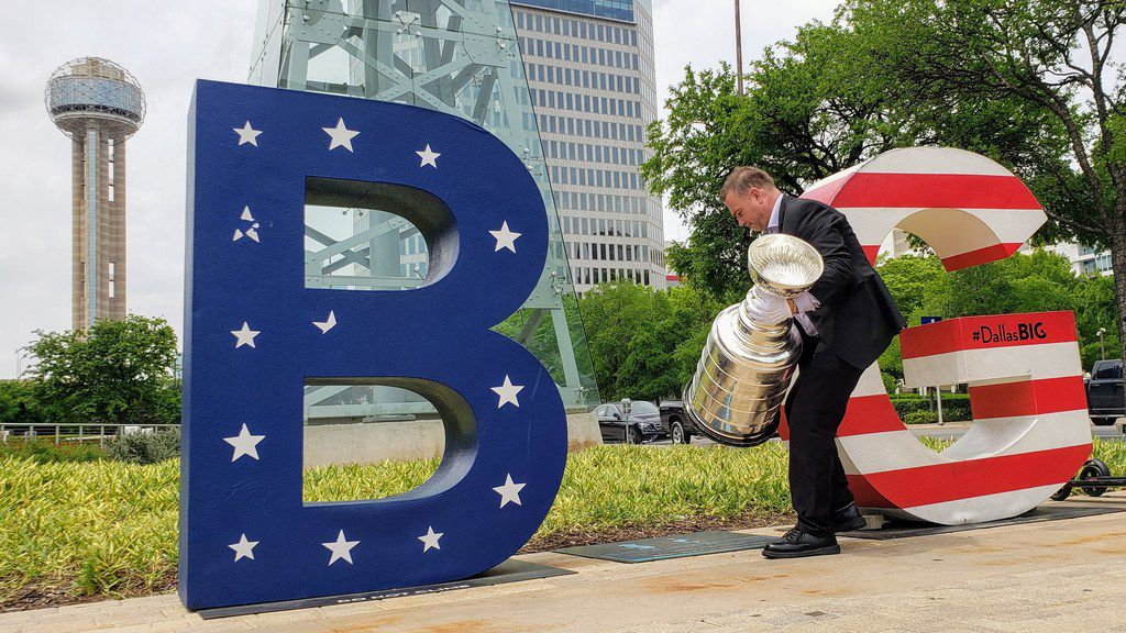 """Howie Borrow, Keeper of the Stanley Cup, approaches a """"B-(i)-G"""" sign near the Omni Hotel in Dallas. Borrow was visiting local TV stations and landmarks in Dallas with the NHL championship trophy."""