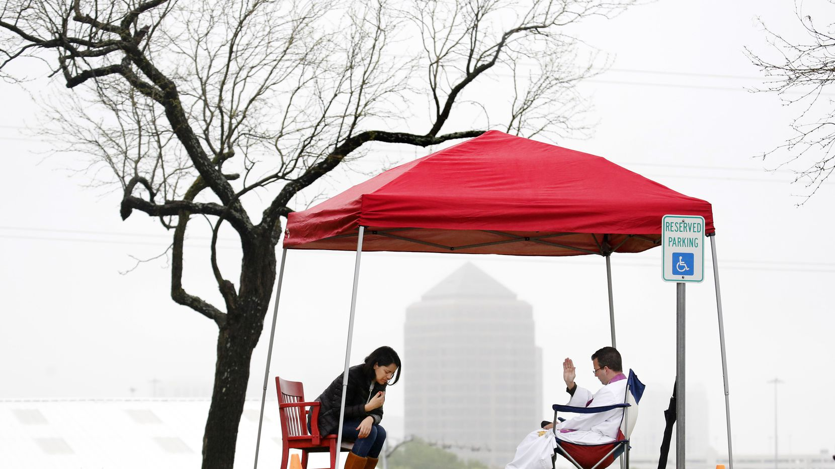 Under a light mist, Regnum Christi priest Fr. Michael Picard (right) prays for Anabel Cardova of Coppell as he listened to her confessions at The Highlands School in Irving, Texas. Priests took confessions from parishioners under tents as they drove up in their cars, Sunday, March 22, 2020. With public spaces shut down amid the coronavirus pandemic, churches are getting creative about providing sacramental relief to their members.