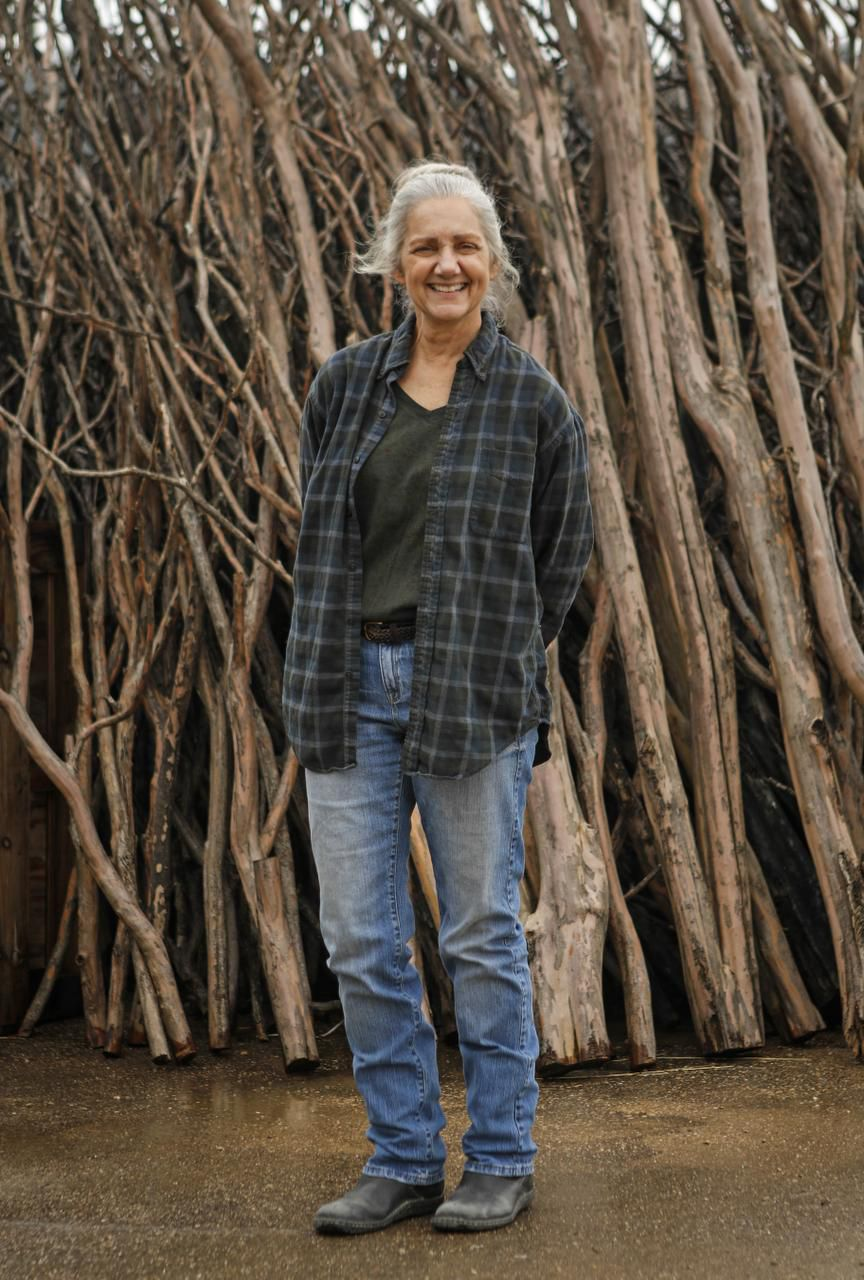 Dallas artist Sherry Owens poses outside her studio in an industrial neighborhood that abuts the east side of the Trinity River levee. Behind her is only a portion of the crape myrtle trunks and limbs she has collected off Dallas' residential streets.