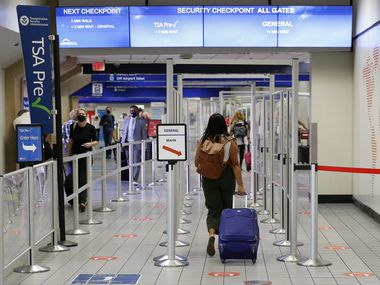 Travelers proceed to a security checkpoint at DFW International Airport.