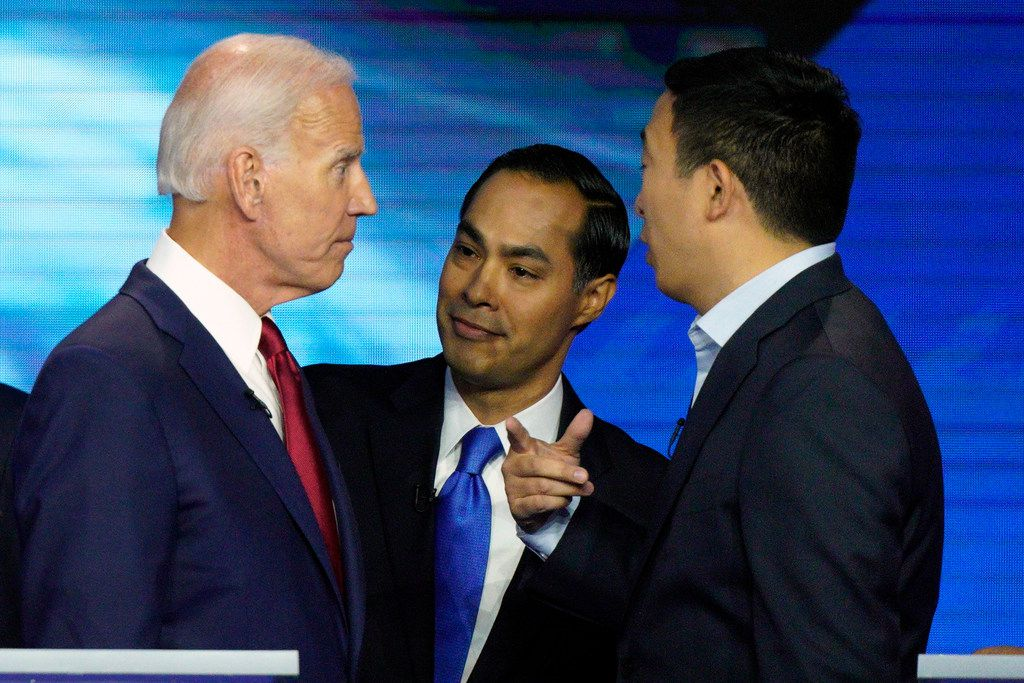 Former Vice President Joe Biden, left, and former Housing and Urban Development Secretary Julian Castro, center, shown listening to Andrew Yang, spent Friday sparring over their exchange on health care at Houston's Democratic presidential debate.