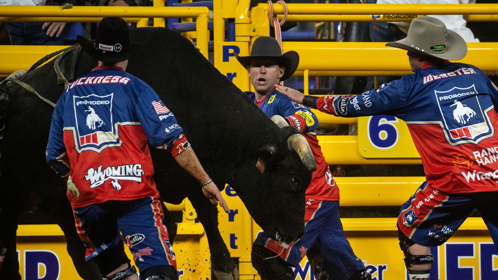 From left, bullfighters Dusty Tuckness, Nate Jestes and Cody Webster redirect Audacious the bull during the bull riding event on the sixth night of the National Finals Rodeo at Globe Life Field in Arlington, Texas, on Tuesday, Dec. 10, 2020.