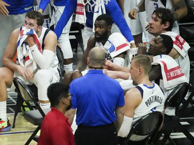 Dallas Mavericks guard Luka Doncic (left) looks up at the scoreboard during a timeout with (from left) forward Tim Hardaway Jr., center Kristaps Porzingis (6), forward Dorian Finney-Smith and center Boban Marjanovic n the fourth quarter of a loss to the LA Clippers in Game 7 of an NBA playoff series at the Staples Center on Sunday, June 6, 2021, in Los Angeles.