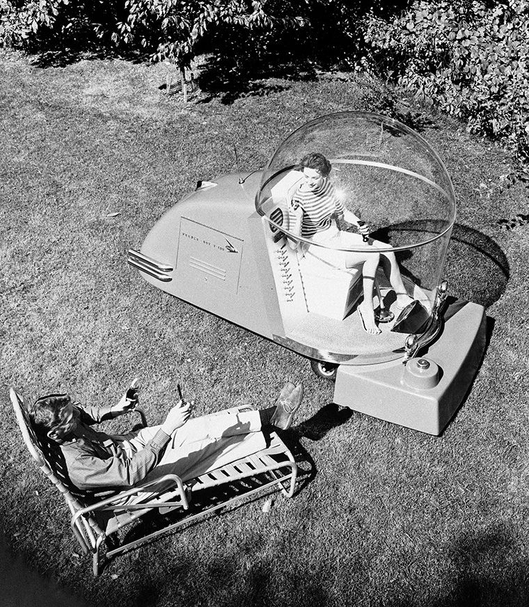 """The """"Power Mower of the Future"""" is demonstrated in Port Washington, Wis., Oct 14, 1957. The lawnmower has a five foot diameter plastic sphere in which the rider sits on an air foam cushioned seat. It has its own electric generating system for operating running lights, a radio telephone, air conditioning and even a cooling system to provide a chilled drink on a hot day. It can be used for many purposes. It can mow the lawn, weed it, feed it, seed it, spray for insects, plow snow and haul equipment. It can even be used as a golf cart. (AP Photo)"""