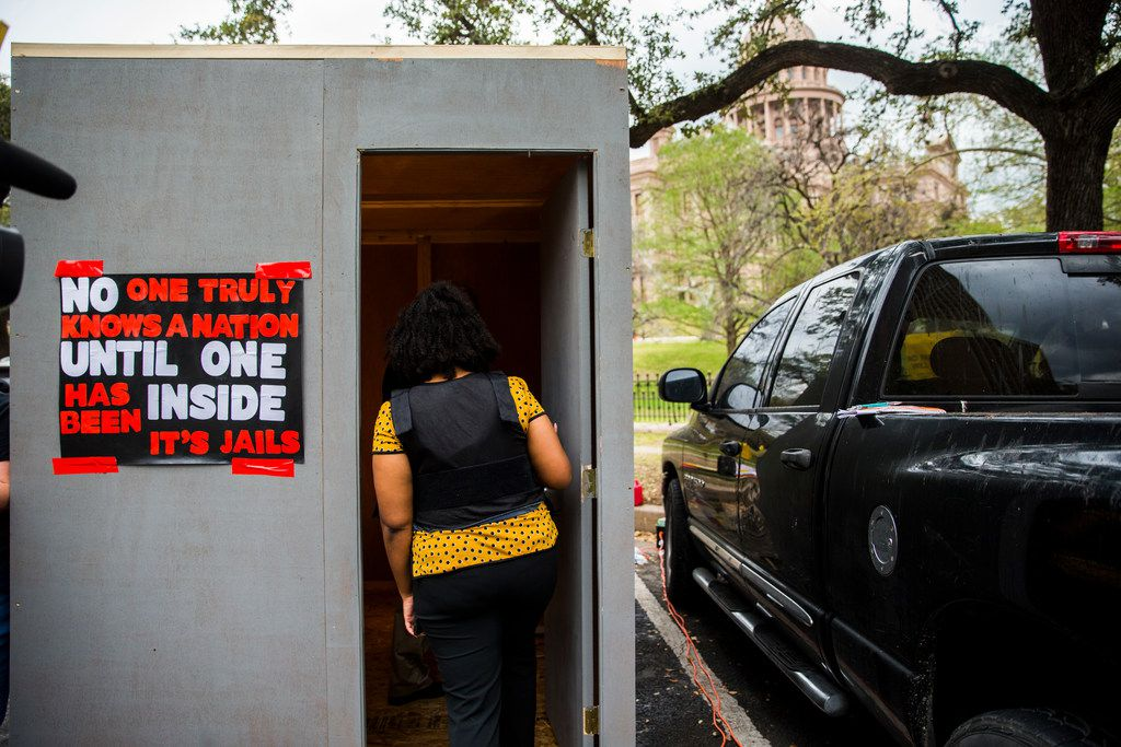 Legislative Aid Jennifer Russell of Houston wears a protective vest like those used by correctional officers as she steps in to a heated, mock prison cell outside the state capitol on Tuesday, March 12, 2019 in Austin. Texas Prisons Air-Conditioning Advocates set up the cell, and challenged people to spend three minutes inside.