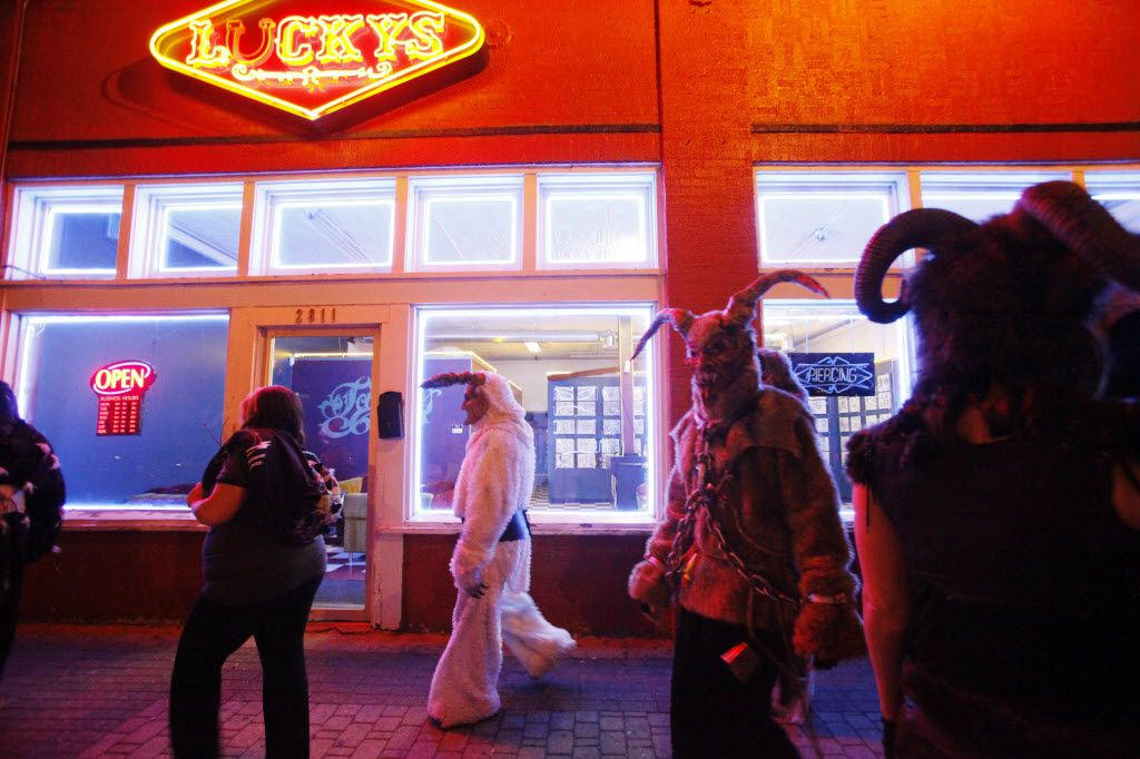 Krampus characters walk passed Lucky's tattoo shop during the Dallas Krampus Walk through the streets of Deep Ellum, organized by the Krampus Society and Dark Hour Haunted House, on Friday, Dec. 5, 2014.