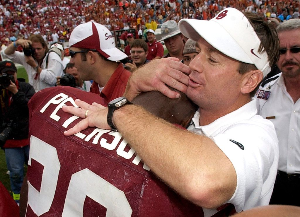 FILE - In this Oct. 9, 2004, file photo, Oklahoma coach Bob Stoops hugs running back Adrian Peterson after beating Texas 12-0, in Dallas. Stoops has decided to retire as Oklahoma's football coach after 18 seasons that included the 2000 national championship and 10 Big 12 Conference titles.  (AP Photo/Tony Gutierrez, File)