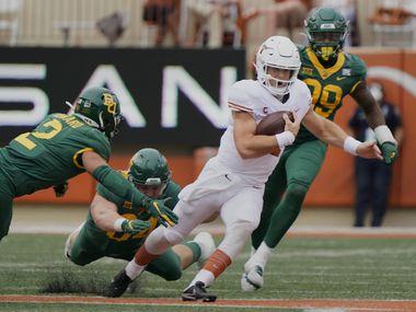 Texas' Sam Ehlinger (11) runs for a first down past Baylor's Terrel Bernard (2) during the first half of an NCAA college football game in Austin, Texas, Saturday, Oct. 24, 2020. (AP Photo/Chuck Burton)