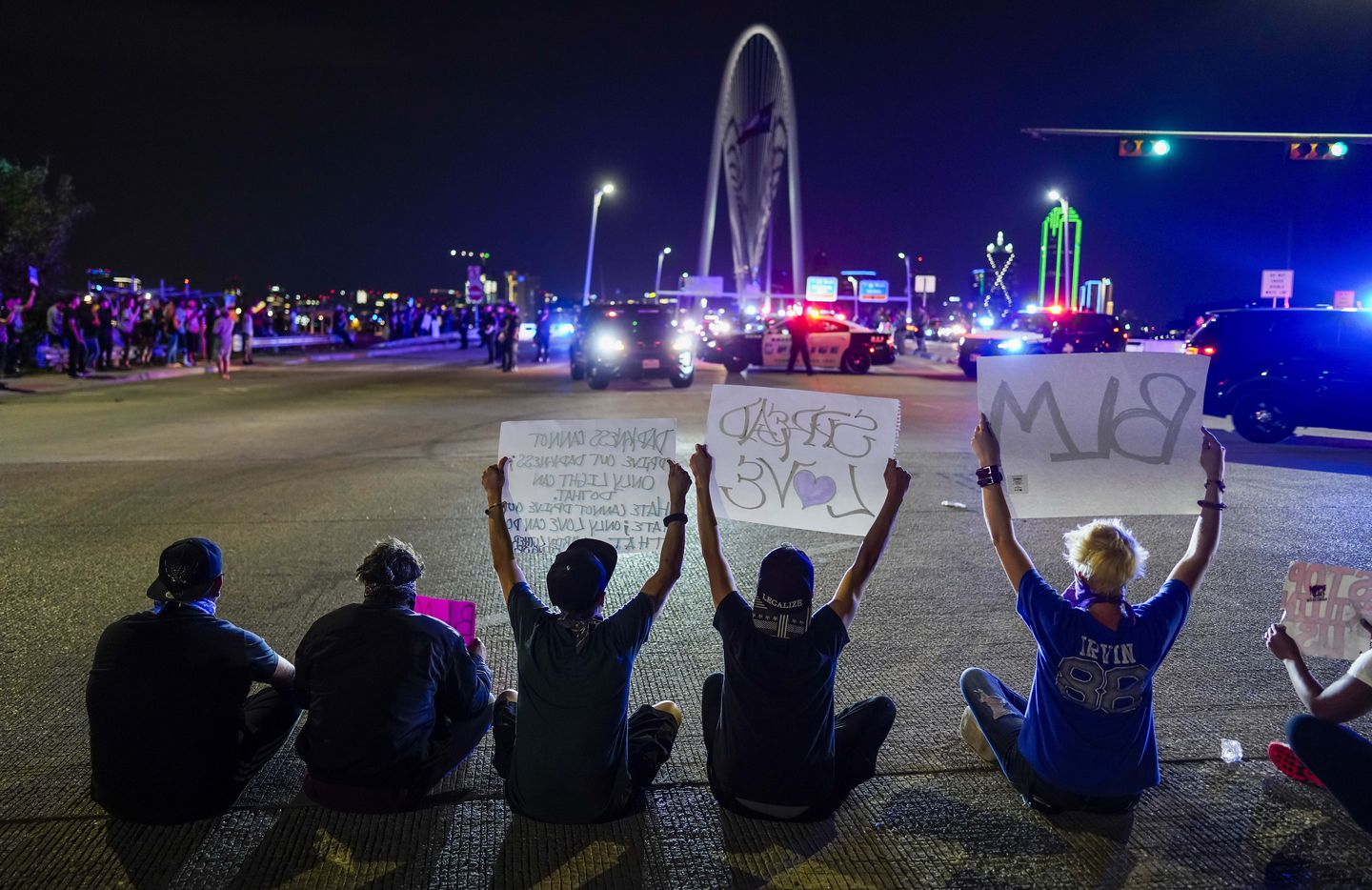 Demonstrators sit in the middle of the street in solidarity as law enforcement officers blocking the western side of the Margaret Helen Hunt Bridge while police conduct mass arrests after protesters demonstrating against police brutality marched onto the bridge on Monday, June 1, 2020, in Dallas. Protests continued Monday, a week after the death of George Floyd.