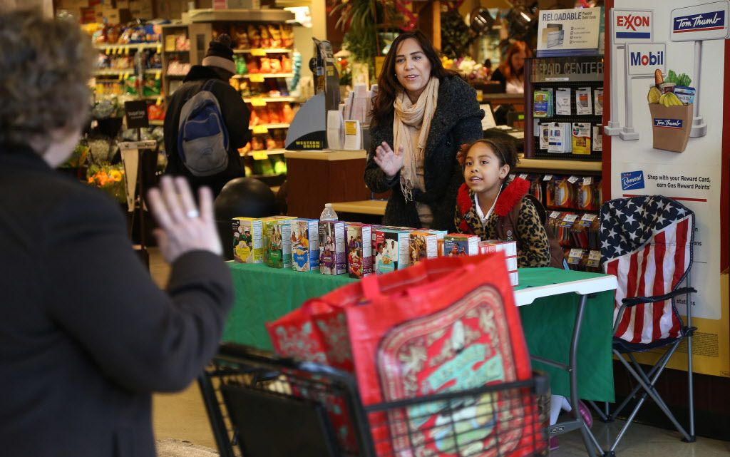 Nadia Perez and her 8-year-old daughter Nadia Perez, with Troop 2809, wave to a customer while at their table selling Girl Scout cookies in the Tom Thumb grocery at Preston and Royal in Dallas, Texas on Thursday, January 23, 2014.
