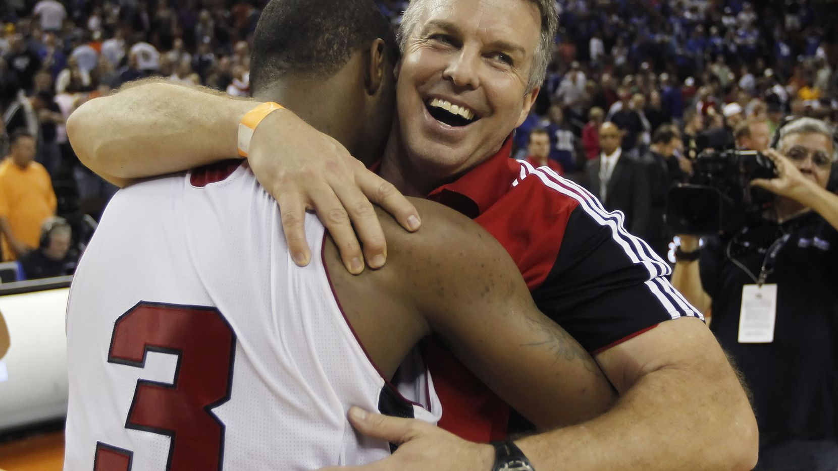 Flower Mound Marcus coach Danny Henderson hugs Marcus Smart (3) after beating Garland Lakeview 40-38 in the Class 5A state championship game in 2011. Smart was named the game's MVP.