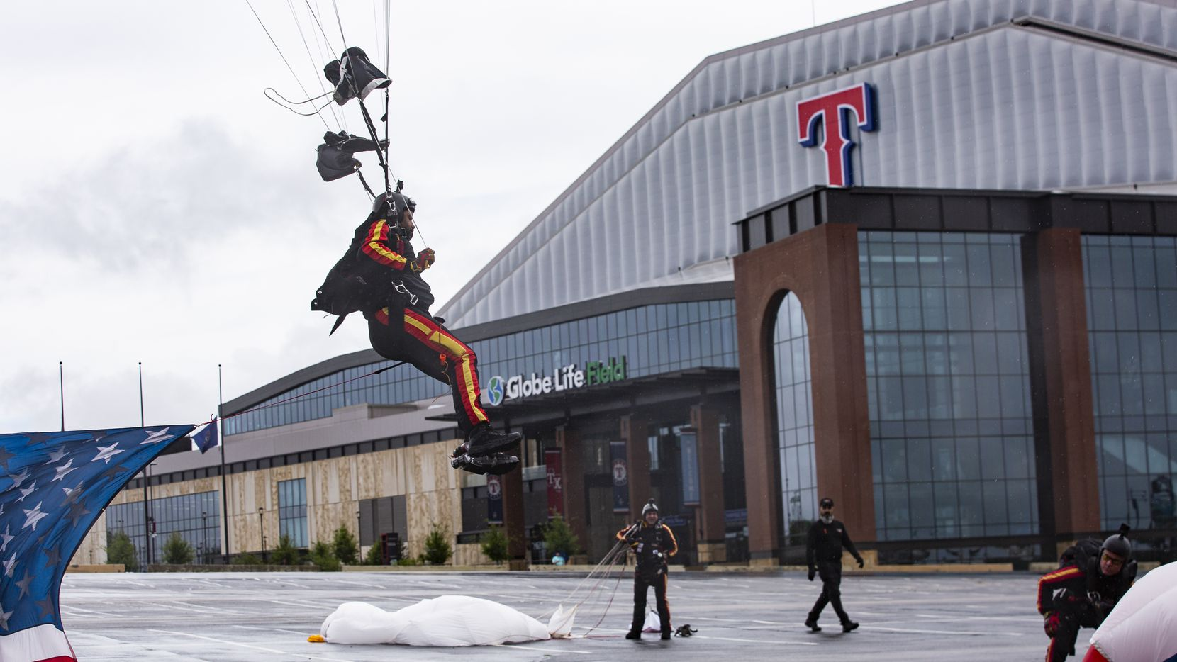 President of the All Veteran Group Mike Elliott lands at the Globe Life Field parking lot after parachuting with an American flag as part of Operation Airdrop on May 25, 2020 in Arlington. The Memorial Day event was held to honor frontline workers and departed military personnel.