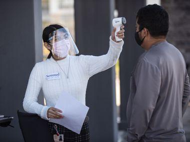 Una empleada de Los Barrios Unidos Health Center revisa la temperatura corporal de un paciente antes de recibir la vacuna contra la influenza, en noviembre de 2020.