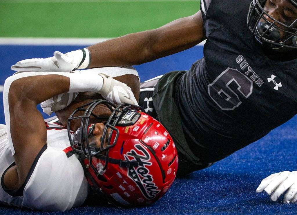 Cedar Hill wide receiver Brian Rainey (left, 12) lies in the endzone after scoring against Denton Guyer right before halftime begins during the Class 6A Division II area-round high school football playoff game at the AT&T Stadium in Arlington, Texas, on Saturday, November 23, 2019. (Lynda M. Gonzalez/The Dallas Morning News)