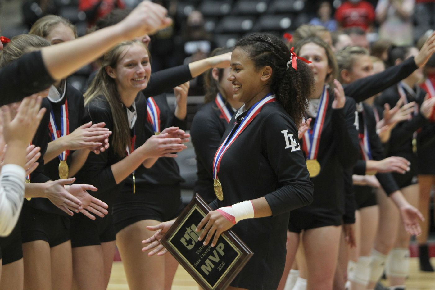Lovejoy's Cecily Bramschreiber (5) was welcomed with open arms by her teammates after she was named MVP in the state 5A final for the 2nd consecutive year following the team's victory over Lamar Fulshear to claim the state title capping their perfect season. The two teams played their Class 5A state championship volleyball match at Curtis Culwell Center in Garland on December 12, 2020. (Steve Hamm/ Special Contributor)