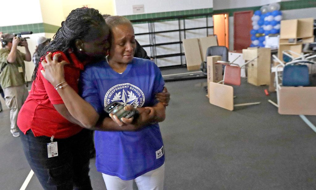 Houston ISD Board of Education Trustee Rhonda Skillern-Jones(right) is hugged by board President Wanda Adams while touring damaged caused by floodwaters at A.G. Hilliard Elementary School.