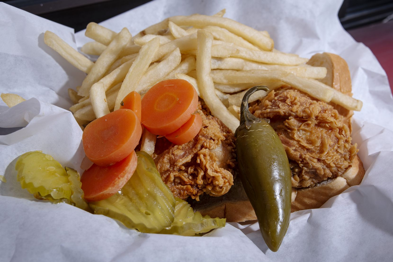 A two-piece dark chicken platter served with fries, pickles, carrots and a jalapeño from Hall's Honey Fried Chicken on West Camp Wisdom Road in Dallas