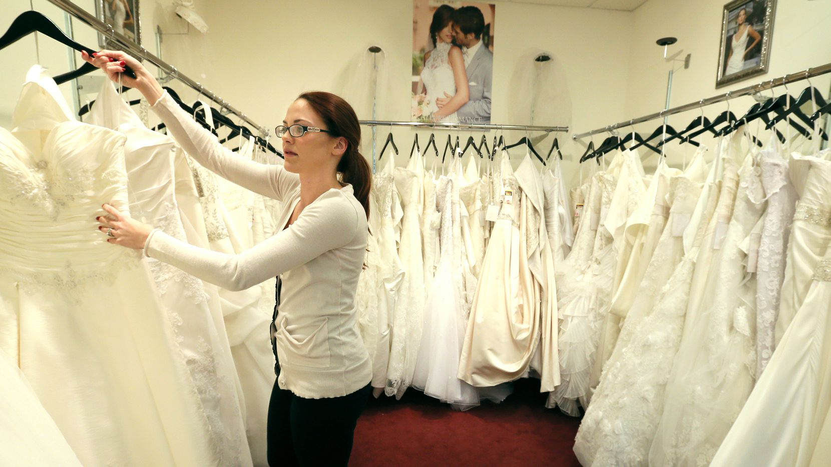 In this photo taken on Wednesday, Jan. 7, 2015, Coming Attractions Bridal & Formal Shop bridal consultant Danielle Snyder hangs a dress at the store in Akron, Ohio. Operators of the northeast Ohio bridal shop linked to an Ebola survivor say the store is closing because it lost significant business and has been stigmatized.  (AP Photo/Akron Beacon Journal, Phil Masturzo )  MANDATORY CREDIT