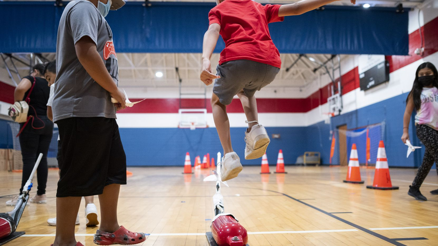 A young boy leaps onto a pouch to propel his paper rocket across a gym at Kleberg-Rylie Recreation Center in far southeast Dallas.