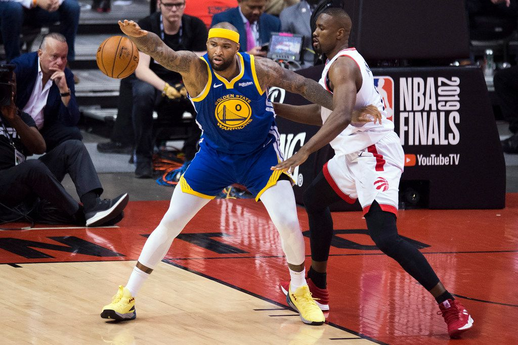 Golden State Warriors center DeMarcus Cousins (0) corrals the ball under pressure from Toronto Raptors centerSerge Ibaka, right, during second-half basketball action in Game 5 of the NBA Finals in Toronto, Monday, June 10, 2019. (Chris Young/The Canadian Press via AP)
