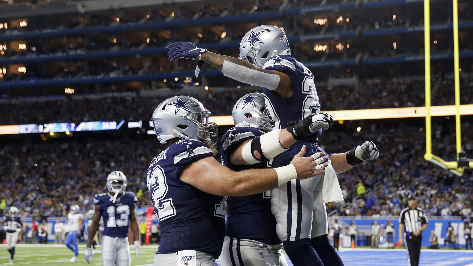 Dallas Cowboys running back Tony Pollard (20) celebrates with Dallas Cowboys center Travis Frederick (72) and Dallas Cowboys offensive guard Zack Martin (70) after scoring a touchdown in a game against the Detroit Lions during the first half of play at Ford Field in Detroit, on Sunday, November 17, 2019.