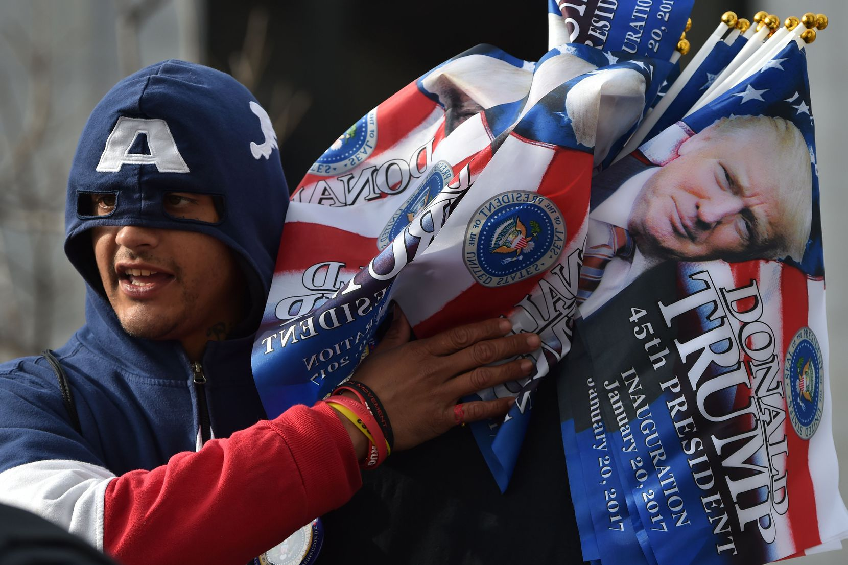 A vendor in a Captain America hoodie sells souvenir flags in a Washington, DC, January 19, 2017, one day ahead of the inauguration of the US President-elect Donald Trump.  / AFP PHOTO / PAUL J. RICHARDSPAUL J. RICHARDS/AFP/Getty Images