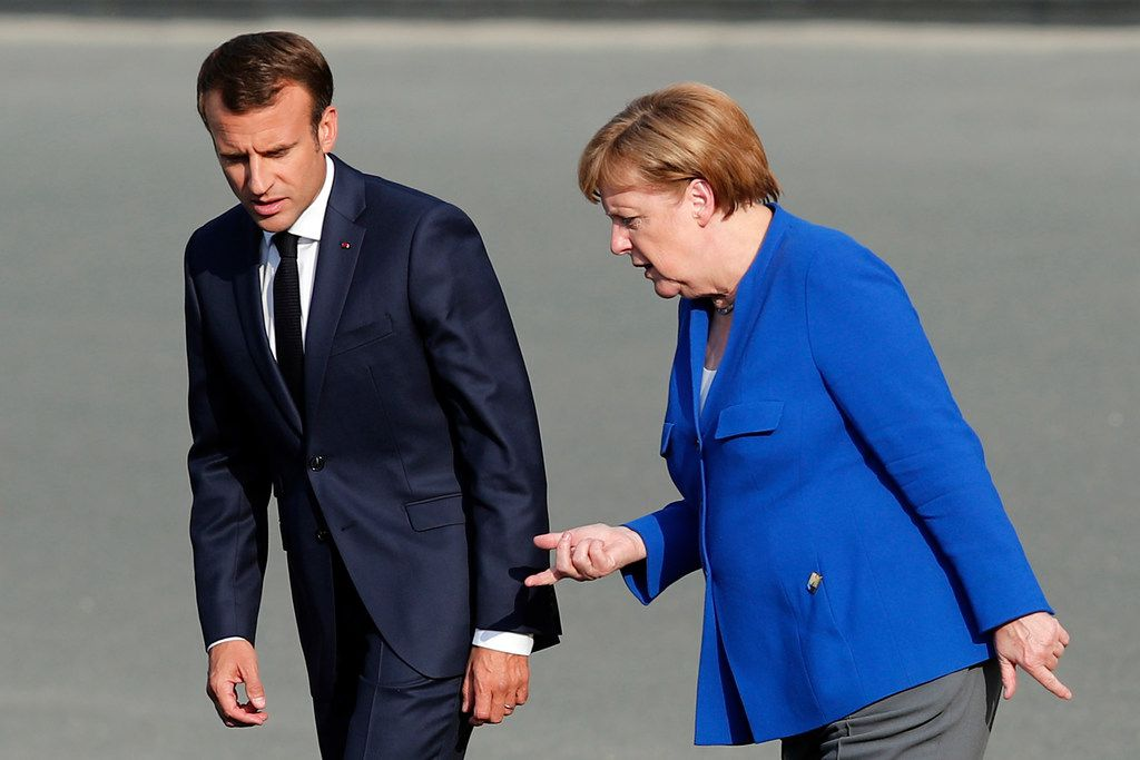 French President Emmanuel Macron (left) and German Chancellor Angela Merkel arrive for a group photo of NATO heads of state and government at Park Cinquantenaire in Brussels on July 11. NATO leaders gathered in Brussels for a two-day summit to discuss Russia, Iraq and their mission in Afghanistan.