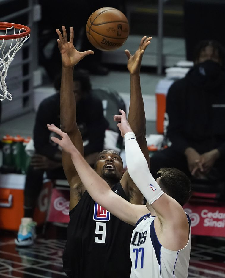 LA Clippers center Serge Ibaka (9) grabs a rebound from Dallas Mavericks guard Luka Doncic (77) during the first half of an NBA playoff basketball game at Staples Center on Tuesday, May 25, 2021, in Los Angeles.