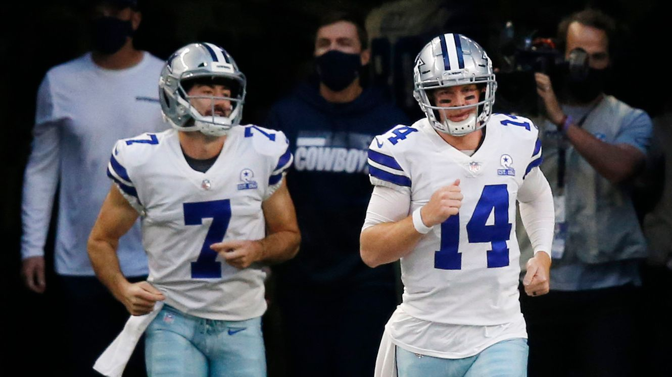 Cowboys quarterbacks Andy Dalton (14) and Ben DiNucci (7) take the field for warmups before a game against the Cardinals at AT&T Stadium on Monday, Oct. 19, 2020, in Arlington.