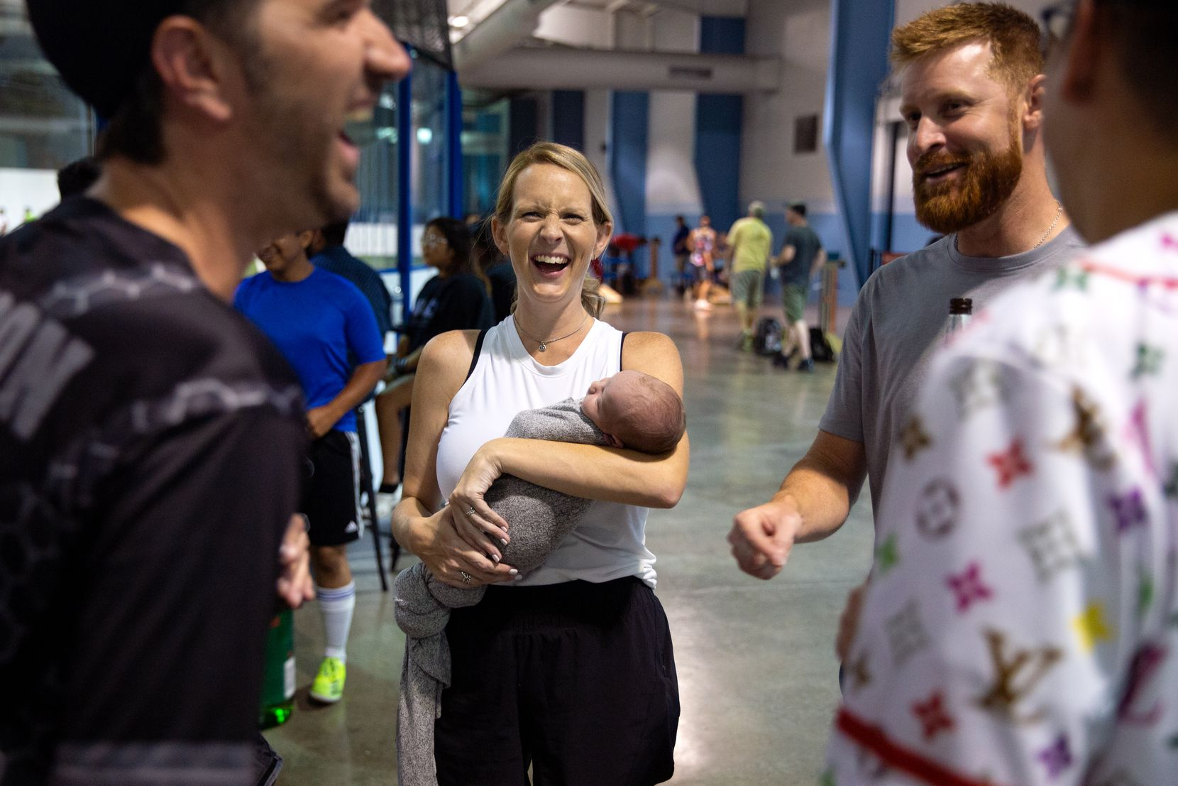 Lynsey Belloso, centered, laughs with fellow cornhole competitors as she carries her 8-day-old son Brody during a cornhole tournament hosted by North Texas Cornhole at the Blue Sky Sports Center in Allen, TX on July 1, 2021. Despite her recent delivery, Lynsey was excited and ready to participate in the tournament.