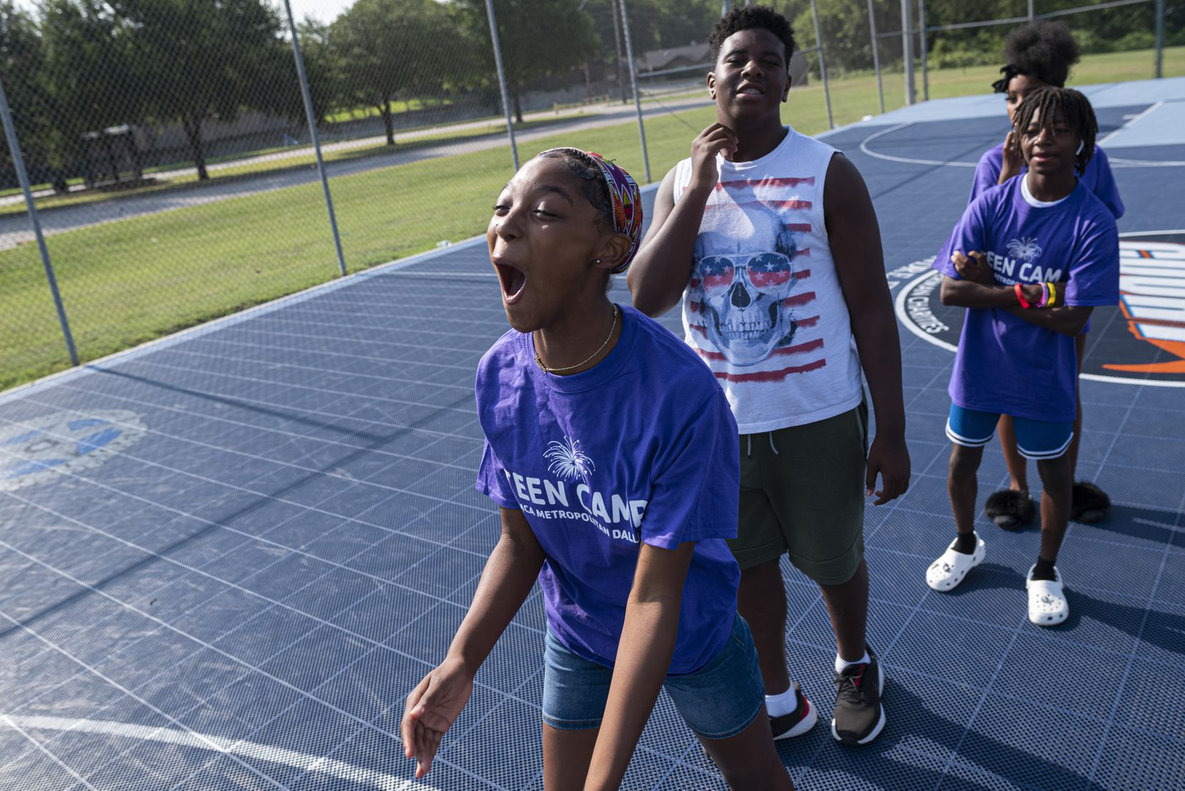 Namoi Robinson, 13, center, reacts after shooting a basketball from the three-point-line during a game of Knockout at the Moorland YMCA in south Dallas. YMCA and Rising Blazers, a UNT Dallas initiative, have partnered up to offer kids ages 10-17 free YMCA membership and summer programs and the Park South and Moorland YMCAs. The free summer programs offer swimming, e-sports and a variety of other activities to keep teens busy.