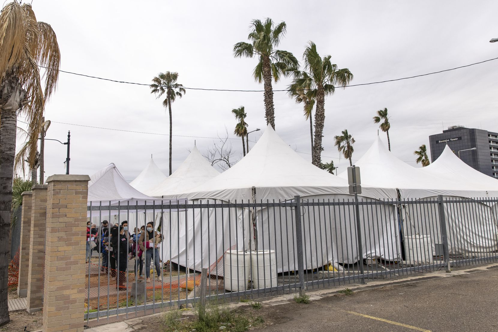 Migrant families with small children wait in line to be tested for COVID-19 at a tent facility set up across the bus station in downtown McAllen, Texas, on Sunday, March 28, 2021. These families were then transported to the nearby respite center operated by Catholic Charities.
