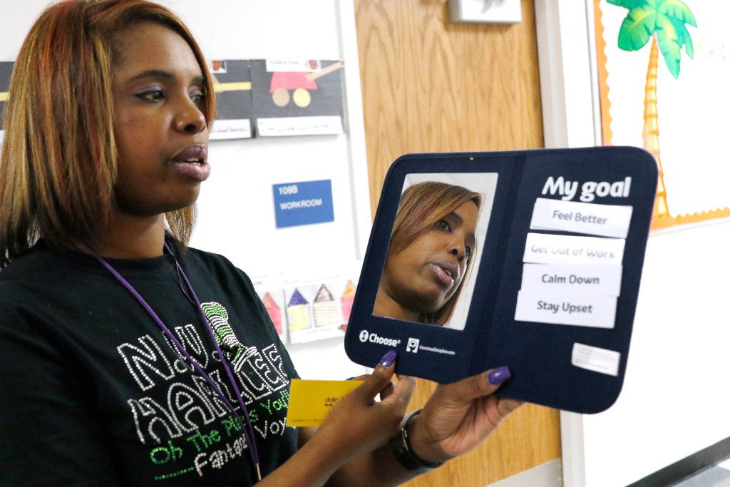 Onjaleke Brown, principal at N.W. Harllee Early Childhood Center in Dallas, holds a self-control board, something she uses with students to help correct their behavior.