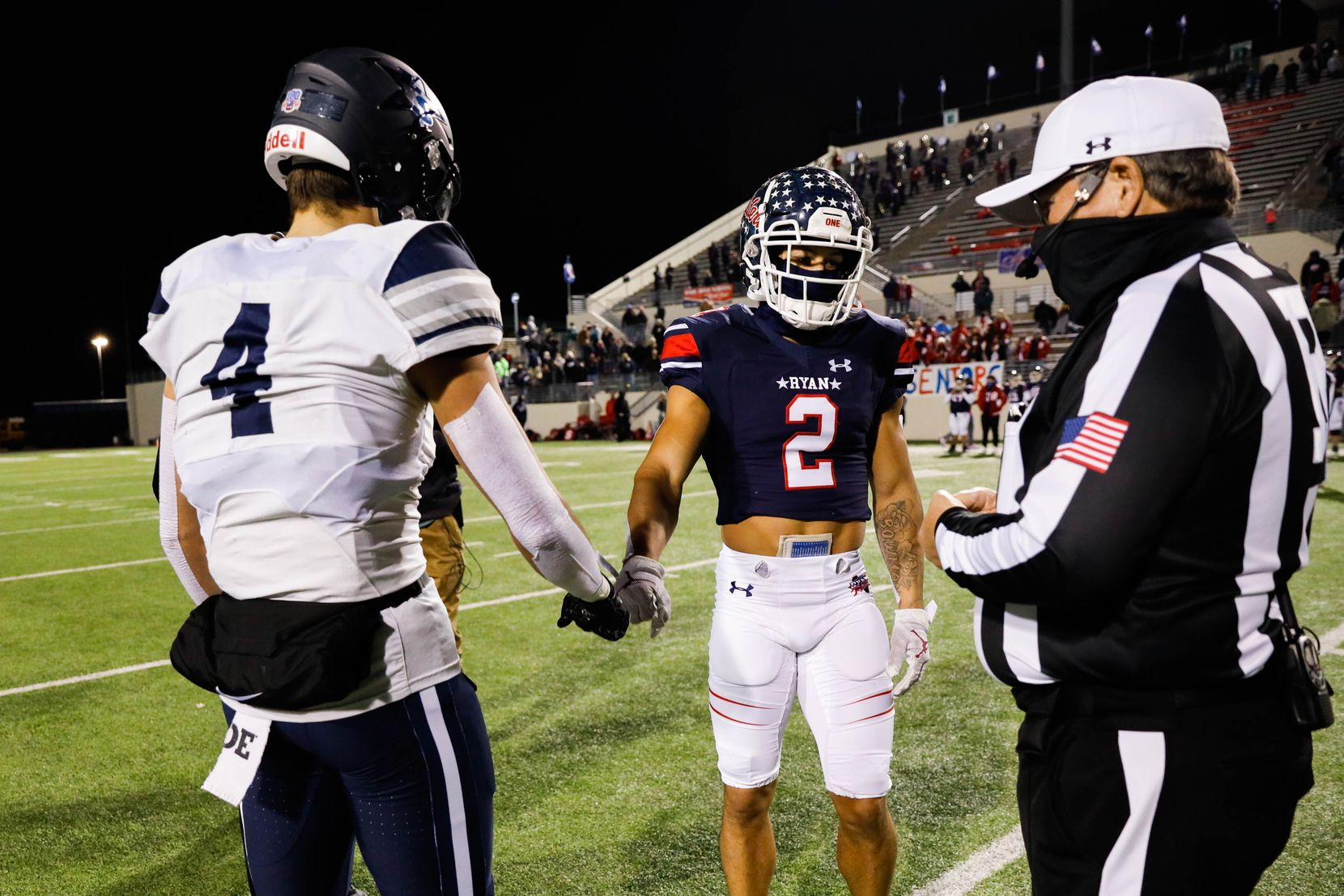 Frisco Lone Star's Trace Bruckler (4) and Denton Ryan's Billy Bowman (2) shake hands during the coin toss at the start of a football game at the C.H. Collins Complex in Denton on Thursday, Dec. 4, 2020. The game is tied at halftime, 14-14. (Juan Figueroa/ The Dallas Morning News)