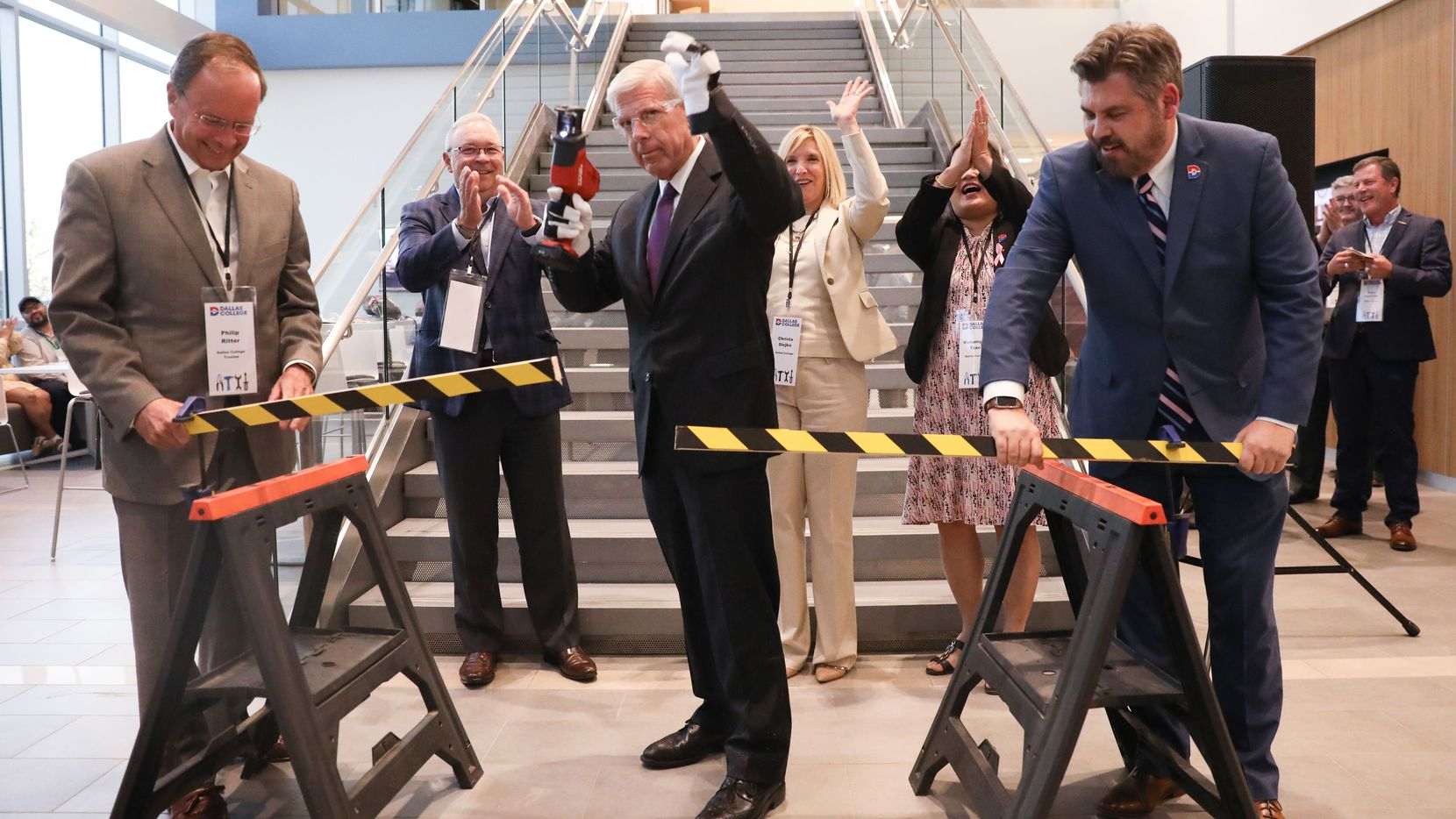 Dallas College Chancellor Joe May saws through a board as a construction-themed take on a ribbon cutting for the Construction Sciences Building at the Dallas College Coppell Center alongside Dallas College and local leadership October 6, 2021.