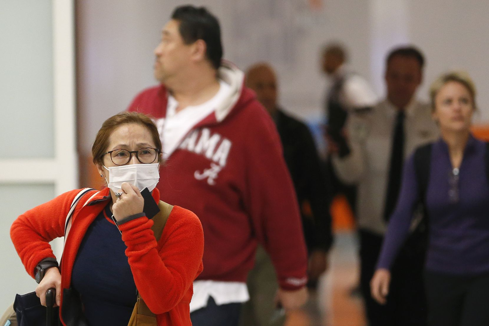 """Vinnie McKinzie of Plano arrived Tuesday at DFW International Airport after a flight home from Hong Kong. """"I bought masks before I went,"""" McKenzie said. """"All sensible people were wearing them."""""""